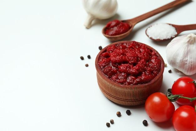 Houten kom met tomatenpuree en ingrediënten op witte ondergrond, ruimte voor tekst