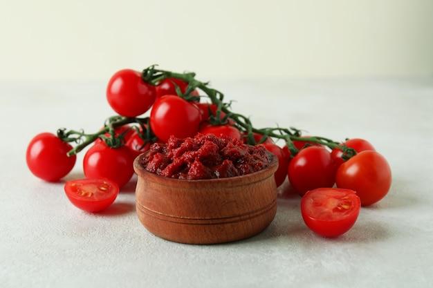 Houten kom met tomatenpuree en tomaten op witte geweven lijst