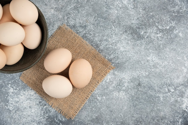 Houten kom met verse biologische rauwe eieren op marmeren oppervlak.