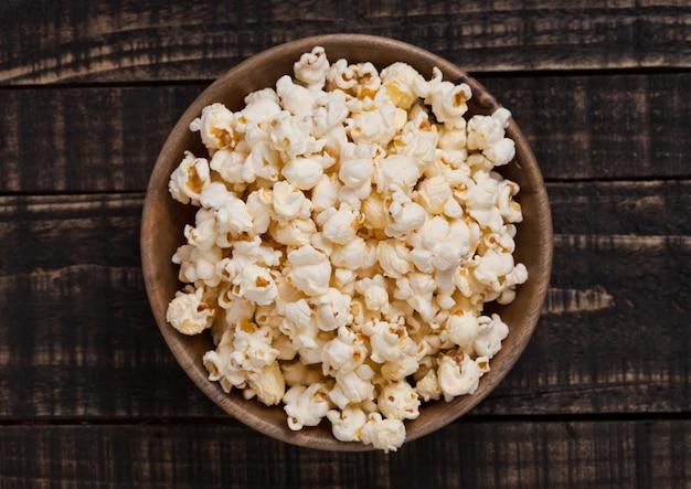 Houten kom met verse gezouten popcorn op houten achtergrond
