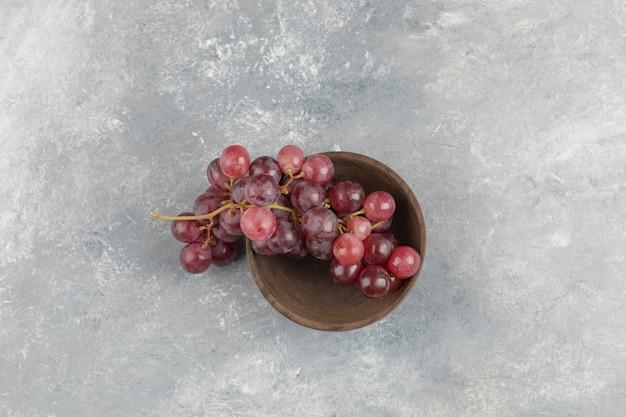 Houten kom met verse rode druiven op marmeren oppervlak.
