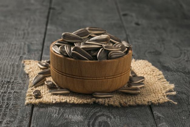 Houten kom met zonnebloempitten op een stuk jute op een houten tafel. de verse opbrengst van zonnebloem.