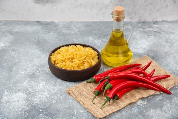 Houten kom rauwe pasta met rode chilipepers en olie op marmer. Gratis Foto