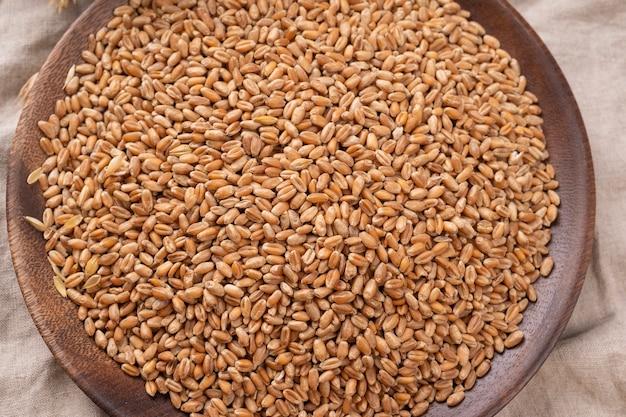 Houten kom tarwekorrels close-up op een tafel. , bovenaanzicht, selectieve aandacht, landbouwconcept
