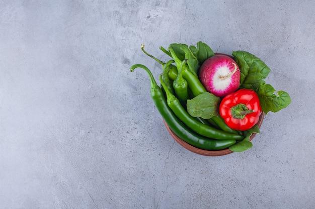 Houten kom van chili en paprika met radijs op blauwe achtergrond.
