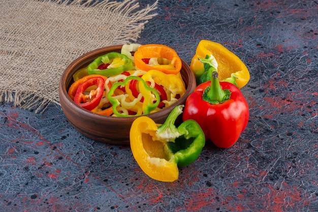 Houten kom vol gehakte kleurrijke paprika's op marmeren oppervlak