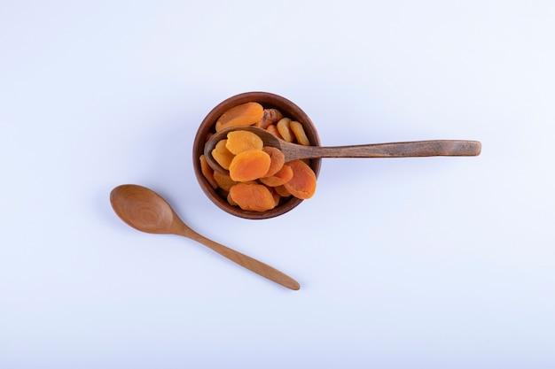 Houten kom vol heerlijke gedroogde abrikozen op wit.