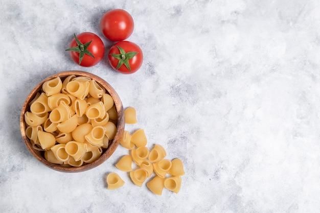 Houten kom vol met ongekookte pasta conchiglie geplaatst op marmeren achtergrond. hoge kwaliteit foto