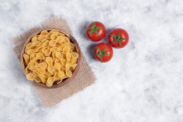 Houten kom vol met rauwe droge farfalle pasta op marmeren tafel. hoge kwaliteit foto