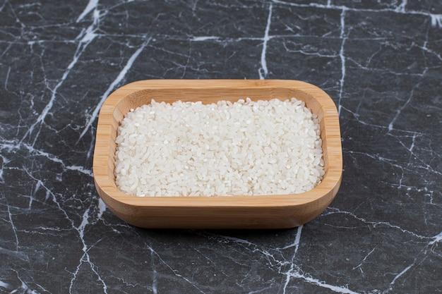 Houten kom vol met rauwe rijst op grijze zwarte steen.