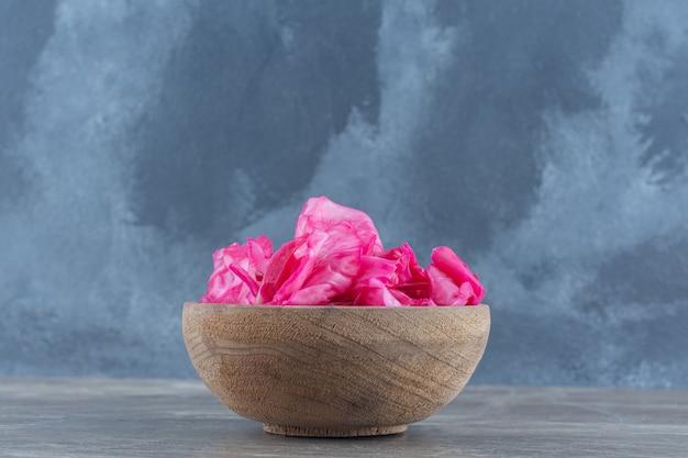 Houten kom vol met roze kool in blik op grijze achtergrond.