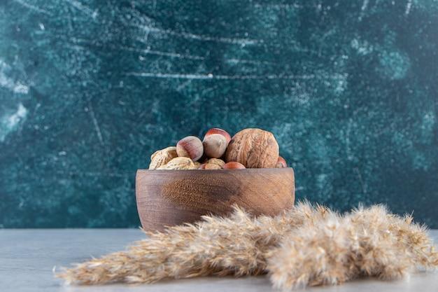 Houten kom vol met verschillende gepelde noten op stenen achtergrond.