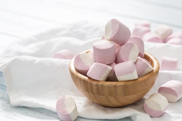 Houten kom vol roze en witte marshmallows met wat verspreid op een wit tafelkleed.