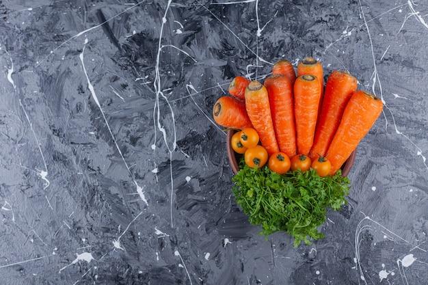 Houten kom wortelen, kerstomaatjes en dille op blauwe achtergrond.