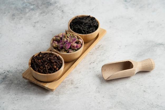 Houten kommen met gedroogde rozen en aftreksel op houten bord.