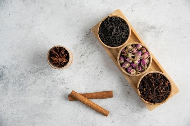 Houten kommen met gedroogde rozen, losse thee en kruidnagel.