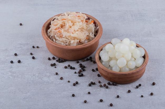 Houten kommen met gefermenteerde zuurkool en uien op stenen tafel.