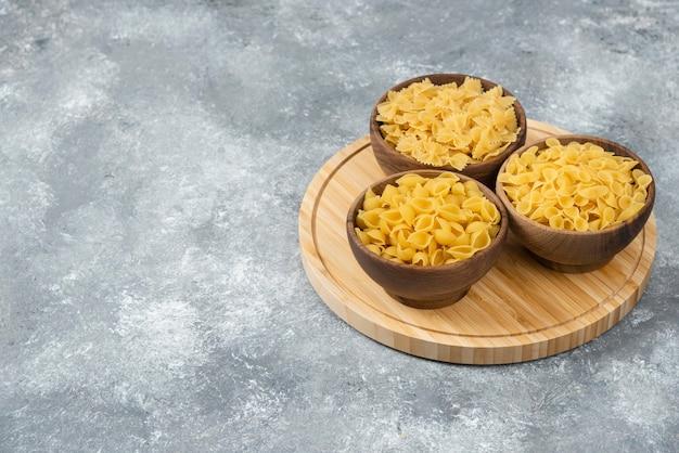 Houten kommen met rauwe droge pasta op marmeren oppervlak.