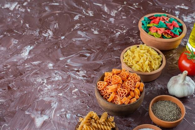 Houten kommen met verschillende droge pasta met groenten op een marmeren ondergrond.