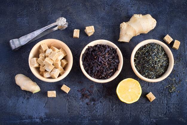 Houten kommen met zwarte en groene thee en suiker, bovenaanzicht