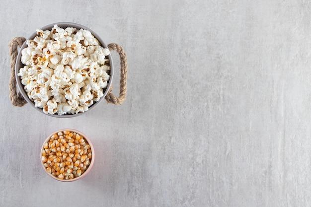 Houten kommen popcorn en rauwe maïskorrels op stenen tafel.