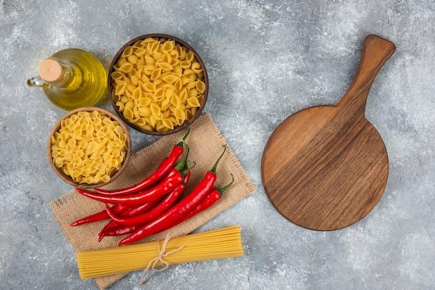Houten kommen rauwe pasta met rode chilipepers op marmer.