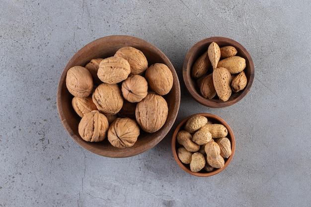 Houten kommen van biologische gepelde walnoten, amandelen en pinda's op stenen oppervlak