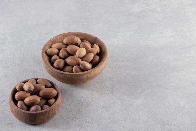 Houten kommen van biologische gepelde walnoten op stenen achtergrond.