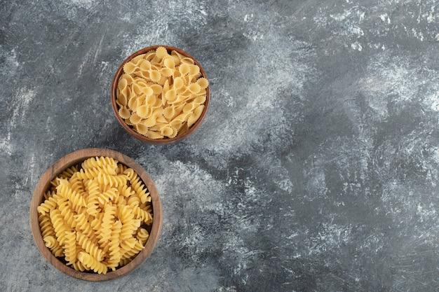 Houten kommen vol rauwe droge fusilli-pasta en farfalle tonde.