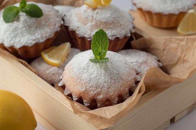 Houten krat met smakelijke citroenmuffins op lijst, close-up