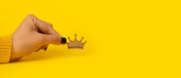 Houten kroon ter beschikking over gele achtergrond, concept voor koning, koninginmacht.