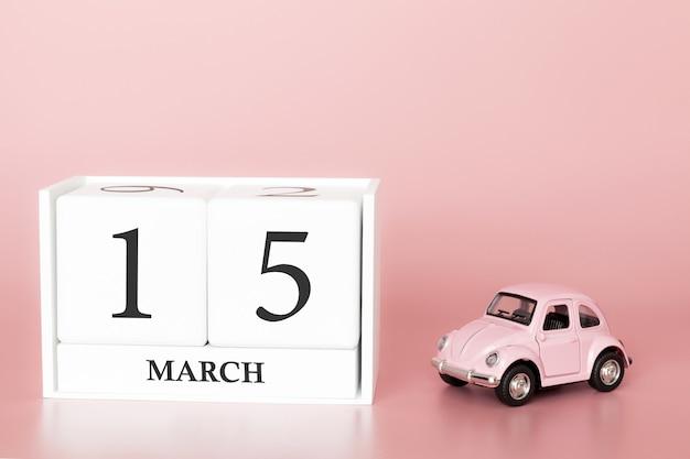 Houten kubus 15 maart. dag 15 van maart maand, kalender op een roze achtergrond met retro auto.
