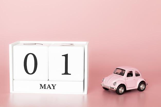 Houten kubus close-up 1 mei. dag 1 van mei maand, kalender op een roze achtergrond met retro auto.