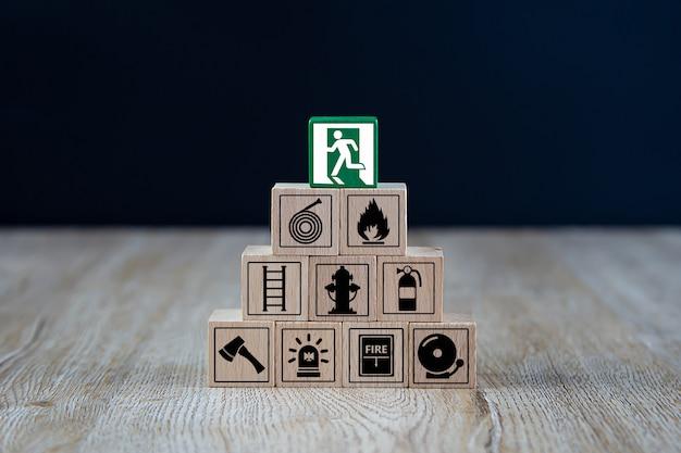 Houten kubus gestapeld in piramidevorm met pictogrammen voor vuur en veiligheid.