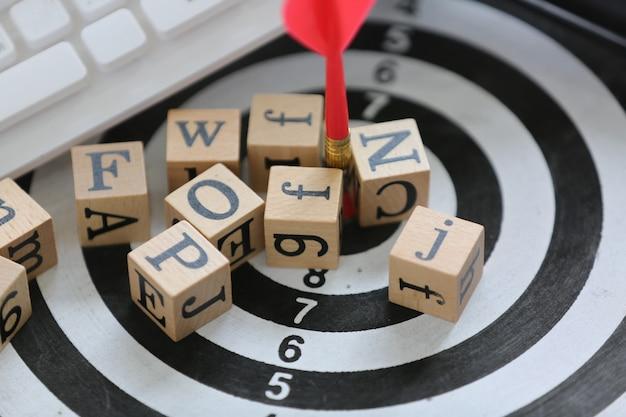 Houten kubus met alfabet op doelbord en wit toetsenbord