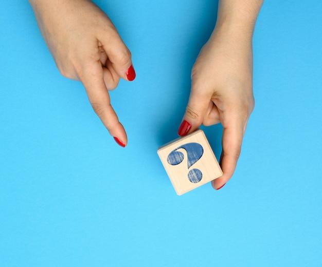 Houten kubus met een vraagteken op een blauwe achtergrond, concept van antwoorden en vragen, spanning