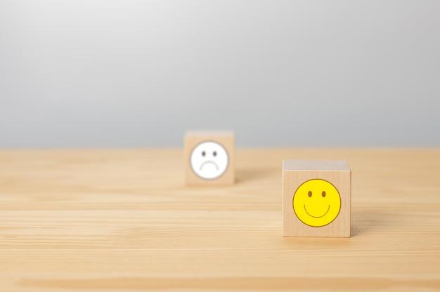 Houten kubus met het gezichtsteken van het glimlachpictogram de kubus met het teken van het negatieve gezichtspictogram is grijs vervaagd
