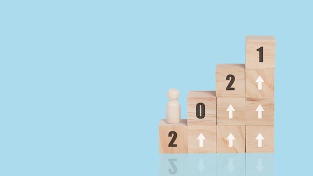 Houten kubus stapelen als opstaptrap met 2021-tekst en pijl-omhoog symbool. business concept groei succes proces. geïsoleerd op blauwe achtergrond.