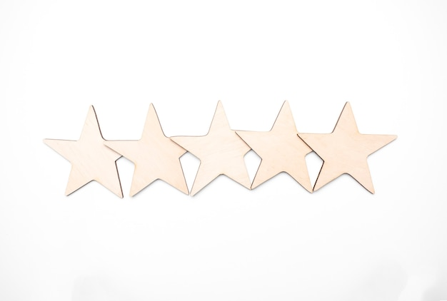 Houten kubus vijf sterrenvorm op houten tafel witte achtergrond. blok 5 sterren beoordeeld als beste service-excellentieconcept. uitmuntendheid klant stem kwaliteit tevredenheid winnaars award.