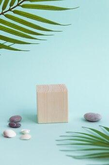 Houten kubus voor spa- en wellnessproduct met palmbladeren en kiezelstenen