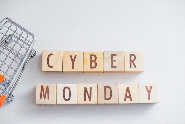Houten kubusblok cyber maandagwoord op lijst met miniboodschappenwagentje.