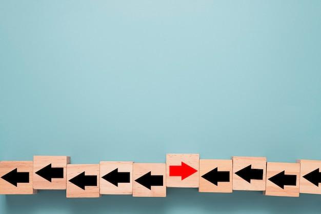 Houten kubusblok dat de rode pijl van het scherm afdrukt, verandert van links naar rechts op een blauwe achtergrond en kopie ruimte.