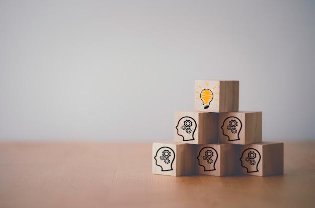 Houten kubusblok dat scherm gloeilamp pictogram op gezicht met versnelling, creatief idee en innovatieconcept afdrukt.
