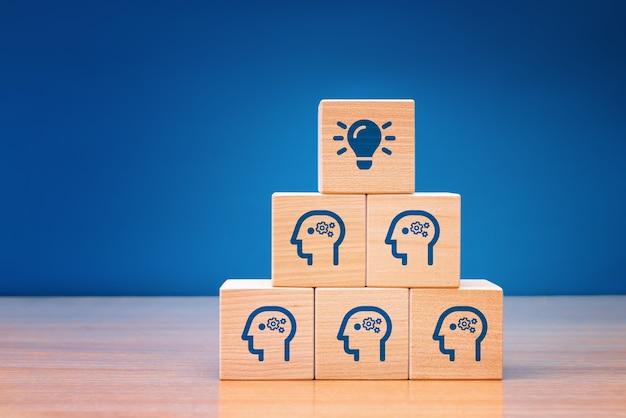 Houten kubusblok met hoofd menselijk symbool en gloeilamp. teamwerk is een gemakkelijke manier om een probleem op te lossen. concept creatief idee.