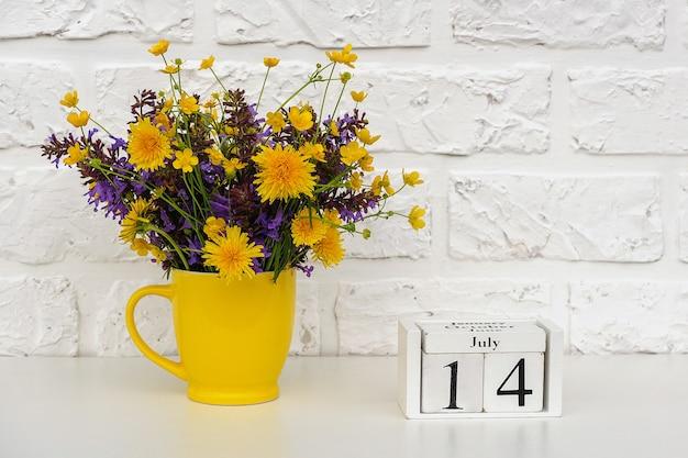 Houten kubuskalender met 14 juli en gele beker met felgekleurde bloemen