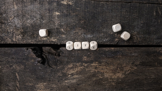 Houten kubussen die het woord life spellen en veranderen in gift in een conceptueel beeld.