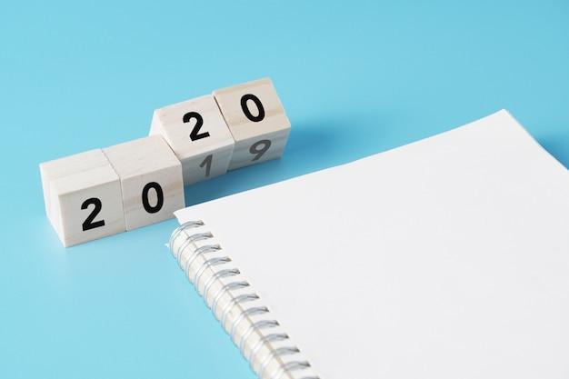 Houten kubussen die van nieuwjaar 2019 tot 2020 concept veranderen met leeg notitieboekje voor takenlijst