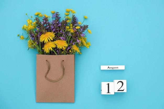 Houten kubussen kalender 12 augustus en veld kleurrijke rustieke bloemen in ambachtelijke pakket op blauw