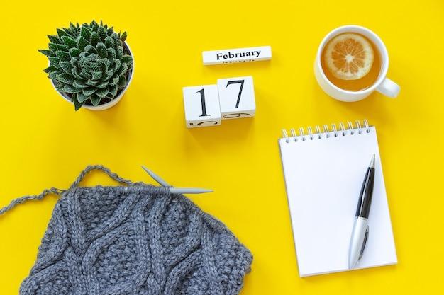 Houten kubussen kalender 17 februari. kopje thee met citroen, lege open blocnote voor tekst. pot met sappige en grijze stof op breinaalden op gele achtergrond. bovenaanzicht plat lag mockup concept