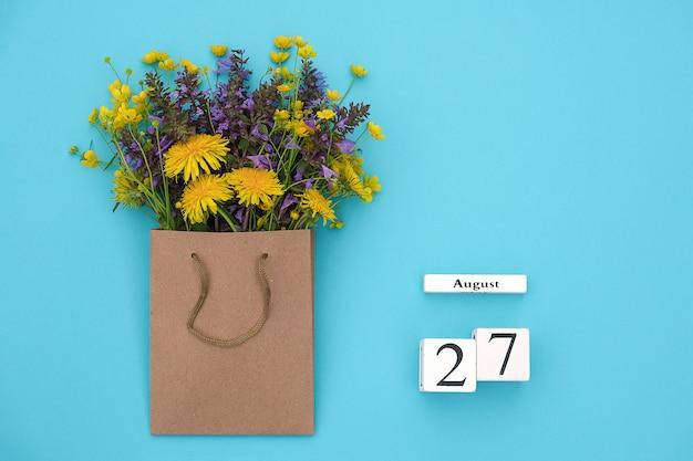Houten kubussen kalender 27 augustus en veld kleurrijke rustieke bloemen in ambachtelijke pakket op blauw
